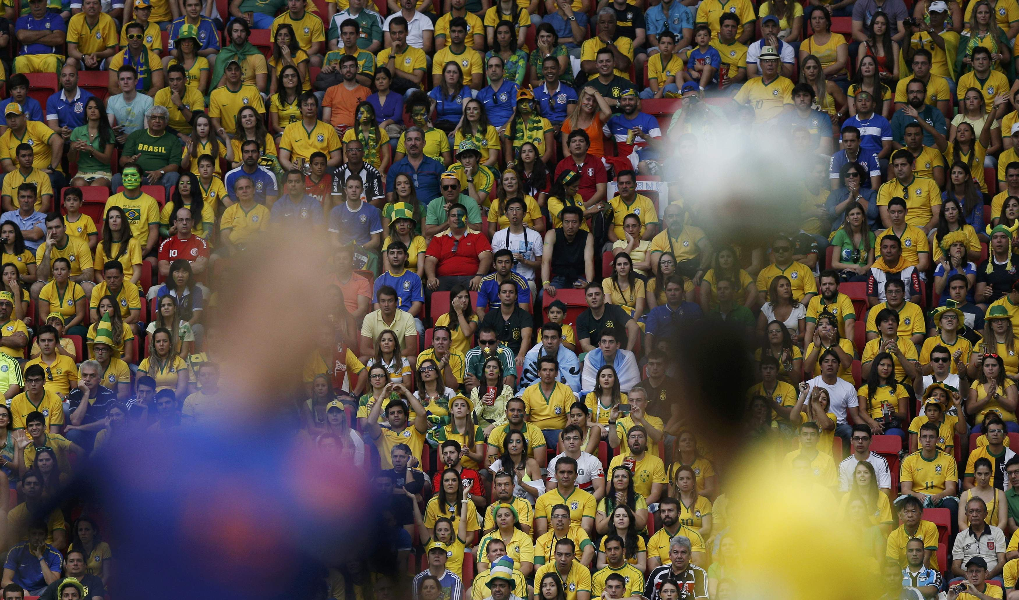 Fans watch as Dirk Kuyt of the Netherlands (L) fights for the ball with Brazil's Oscar during their 2014 World Cup third-place playoff at the Brasilia national stadium in Brasilia July 12, 2014. REUTERS/Ueslei Marcelino (BRAZIL  - Tags: SOCCER SPORT WORLD CUP TPX IMAGES OF THE DAY)        TOPCUP - RTR3YBND